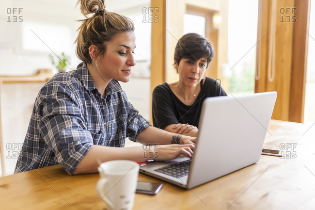 Two beautiful and young women having breakfast at home and using the laptop