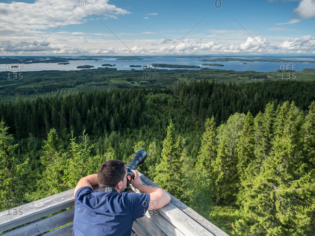 Back view of young man taking photos of beautiful landscape on digital camera in Finland