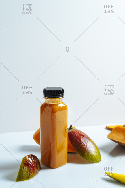 Mango and pumpkin vegan smoothie on bottle. Surrounded by fruits and vegetables, healthy life concept