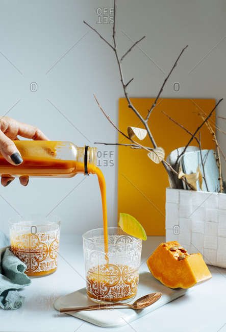 Woman serving fresh mango smoothie into a glass