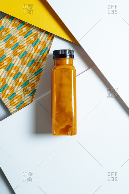 Mango and pumpkin smoothie bottle over retro style geometric textures. From above