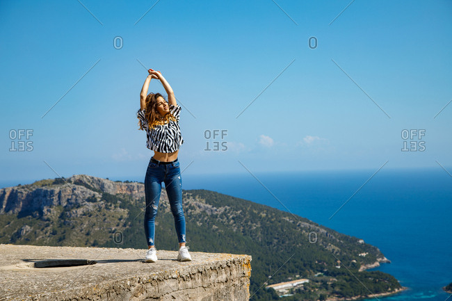 Pretty young female in casual outfit enjoying sun while standing on top of cement block against cloudless blue sky near sea