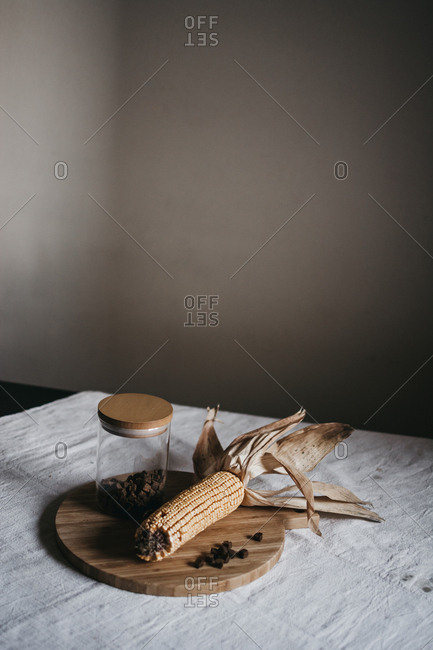 Dried corn on cob placed on wooden board near jar with brown spice on kitchen table