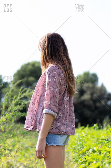 Side view of anonymous female teenager in casual outfit looking away while standing in field on sunny day in Catalonia, Spain