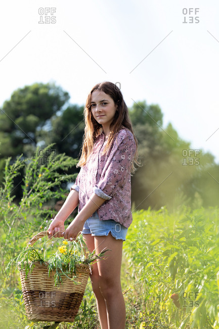 Side view of female teenager in casual outfit looking at camera while standing in field and holding basket with green herbs on sunny day in Catalonia, Spain