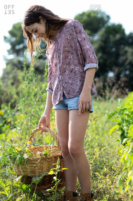 Side view of female teenager in casual outfit smiling and looking away while standing in field and holding basket with green herbs on sunny day in Catalonia, Spain