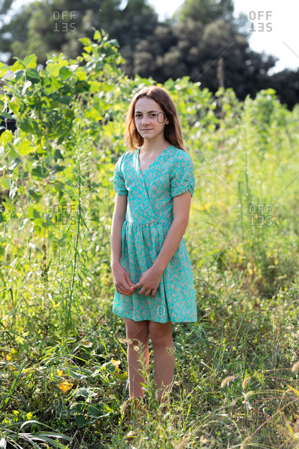 Portrait of teen girl in blue dress among plants in field on farm in Catalonia, Spain