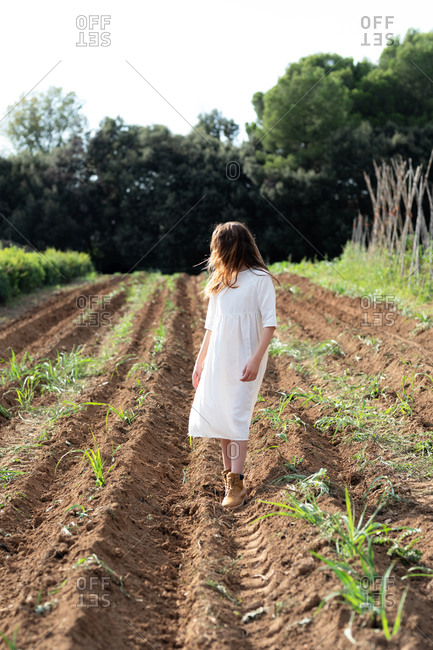 Anonymous teen girl walking near sprouts on agricultural field in orchard in Catalonia, Spain