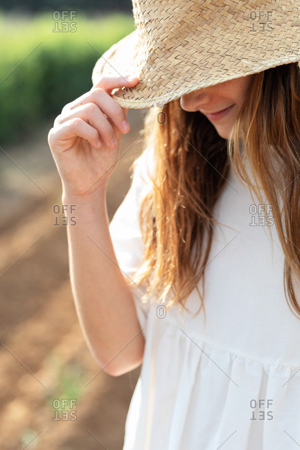 Anonymous teen girl hiding her face with a hat on agricultural field in orchard in Catalonia, Spain