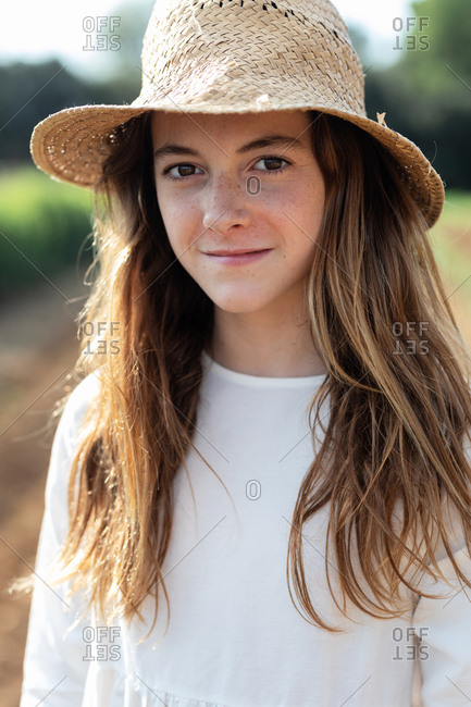 Portrait of teen girl with a hat looking at camera on agricultural field in orchard in Catalonia, Spain