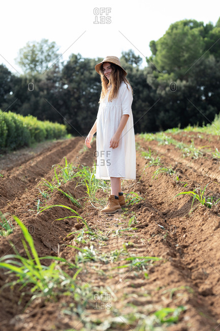 Teen girl with hat walking near sprouts on agricultural field in orchard in Catalonia, Spain