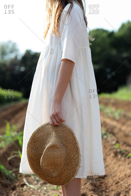 Crop view of anonymous teen girl holding a hat near sprouts on agricultural field in orchard in Catalonia, Spain