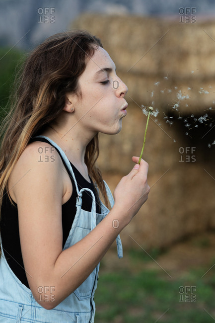 Side view of female teenager in casual outfit blowing dandelion with closed eyes while spending time in countryside in Catalonia, Spain