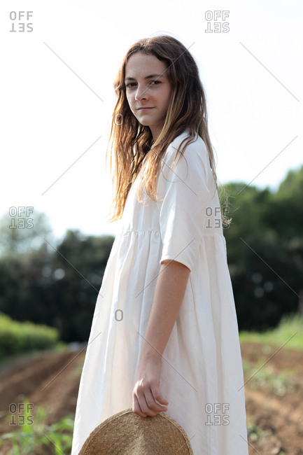 Teen girl with hat near sprouts on agricultural field in orchard in Catalonia, Spain