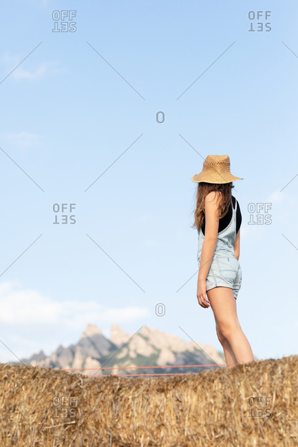 Anonymous young beautiful female in casual clothes and hat standing on bale of hay