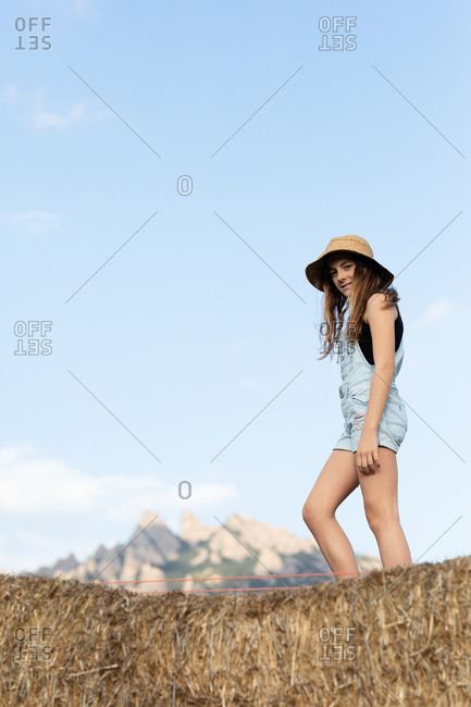 Young happy beautiful female in casual clothes and hat standing on bale of hay and looking at camera