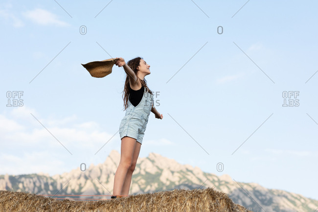 Young happy beautiful female in casual clothes throwing a hat while standing on bale of hay