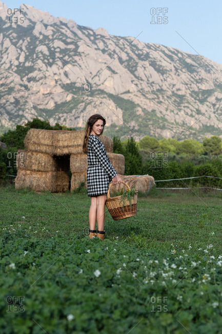 Portrait of female teenager in casual outfit standing in field and holding basket with green herbs on sunny day in Catalonia, Spain