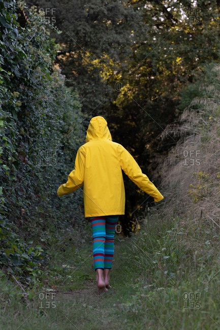 Back view of young attractive barefoot female in yellow jacket walking in woods alone