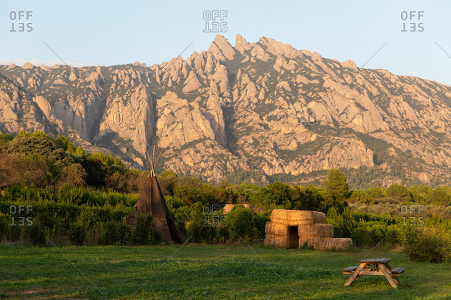 Landscape of rural with bale of hay, tent and wooden table near beautiful rocks