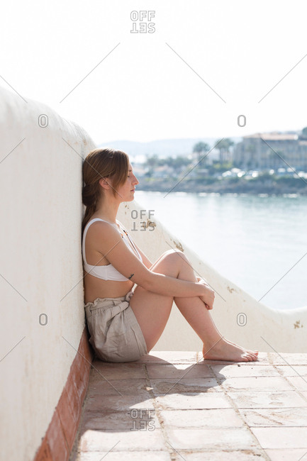 Woman relaxing near plaster railing