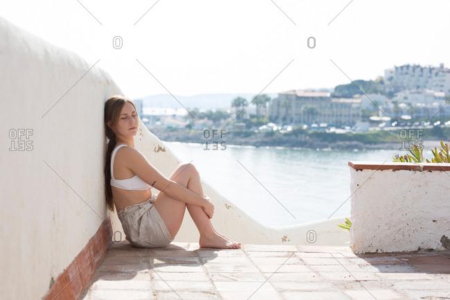 Woman relaxing near plaster railing
