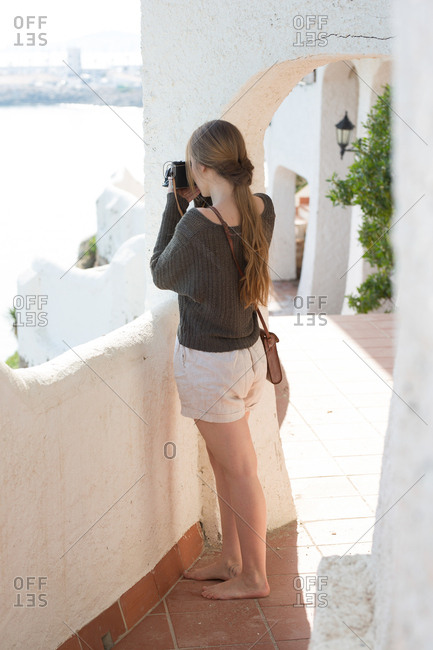 Barefoot female taking pictures from terrace