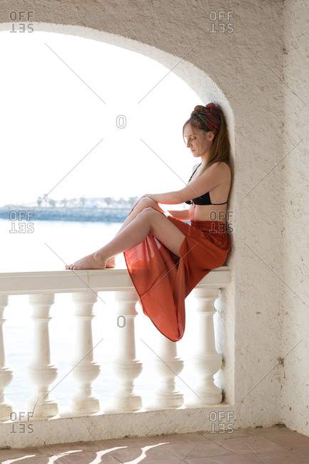 Side view of slim young woman in swimwear and skirt resting and sitting on railing in arch of old building near sea on sunny day on resort