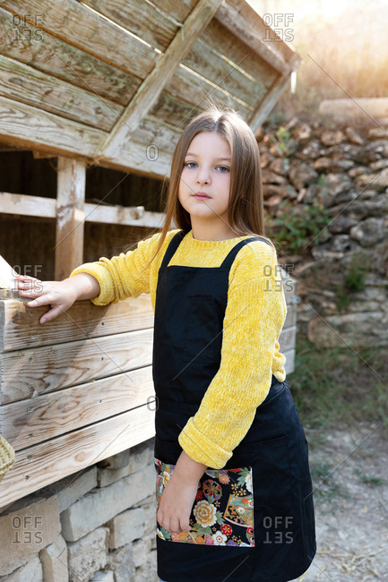 Girl standing near chicken nest wearing an apron on sunny day on farm