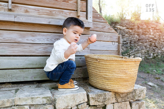 Side view of little boy playing with chicken eggs while sitting on haunches near wicker outside shed in countryside
