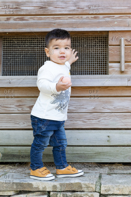 Baby boy in casual outfit touching net and holding a egg on window of wooden shed