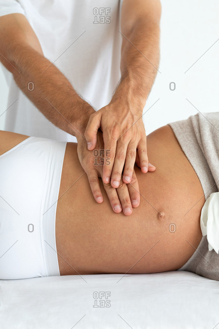 Crop young sensual pregnant woman relaxing while husband massaging belly of wife isolated on white background