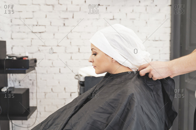 Stylist washing hairs to young lady