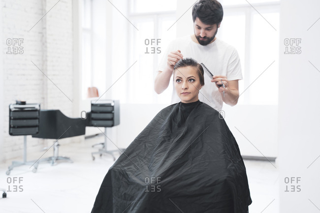 Hairdresser cuts woman's hair with scissors