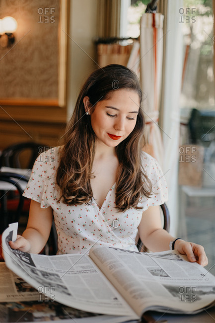 Young pretty lady reading a newspaper in a vintage coffee shop
