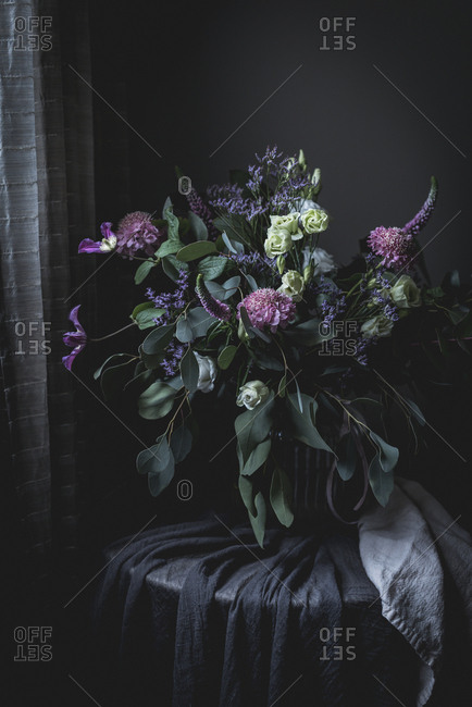 Amazing bouquet of flowers on a table into a dark vintage room