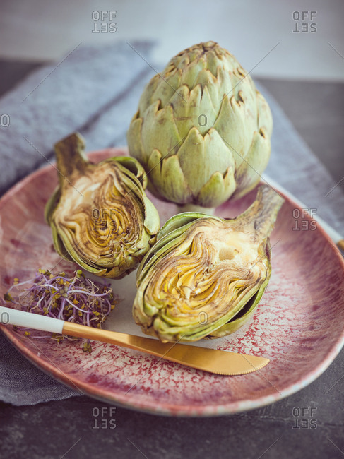 Small knife and cut and whole fresh artichokes placed on pink ceramic plate on table
