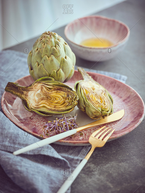Small knife and fork and cut and whole fresh artichokes placed on pink ceramic plate on table