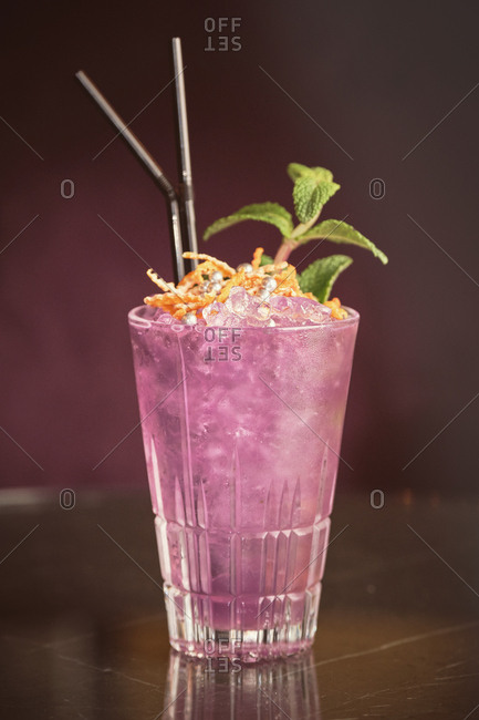 Glass of cold pink cocktail with mint leaves and orange peel placed on counter in bar