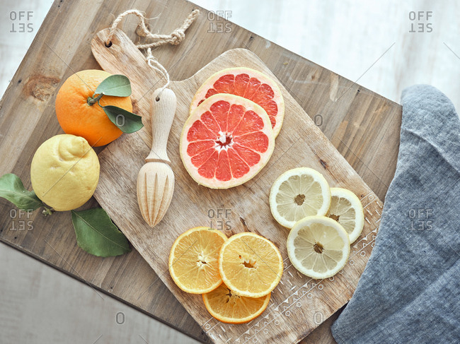 From above composition of citrus fruits slices, blue kitchen towel and reamer placed on wooden board