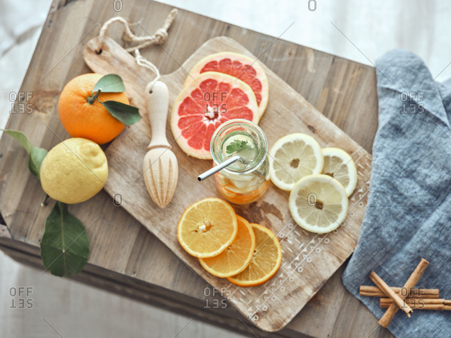 From above composition of lemons, grapefruit and orange lemonade in glass bottle in wooden board