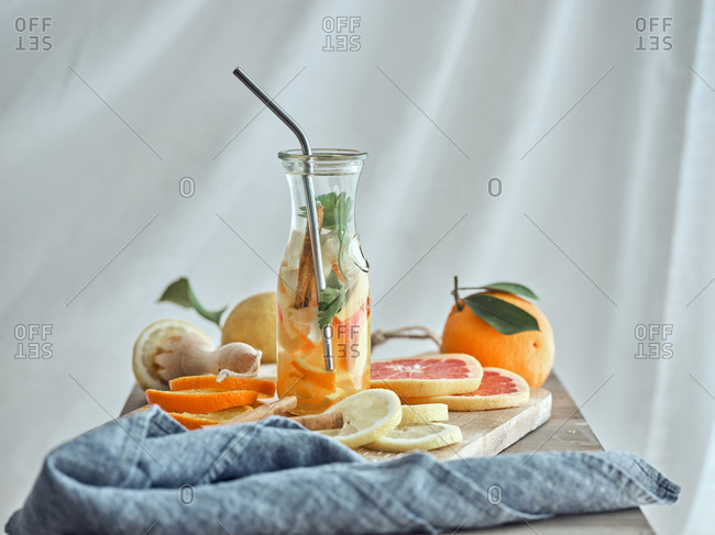 From above composition of lemons, grapefruit and orange lemonade in glass bottle in wooden board