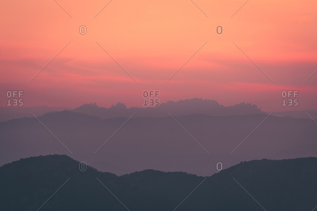 Bright cloudy sky over silhouette of mountain range during sundown in nature