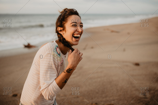 Young lady in casual outfit touching braid and laughing out loud while standing on sandy seashore