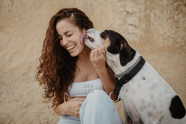 Funny dog licking cheek of excited young lady against weathered building wall on street