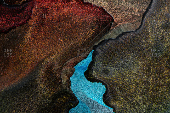 Spills of multicolored metallic dye mixing and spreading on black background