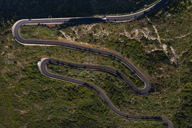 Aerial view of empty winding country road in green remote sunny countryside of Spain