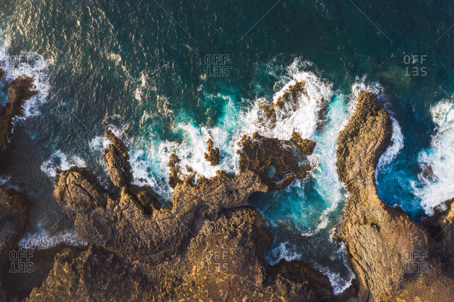 Aerial view of rocky coast in Spain with dashing majestic foamy waves in sunlight