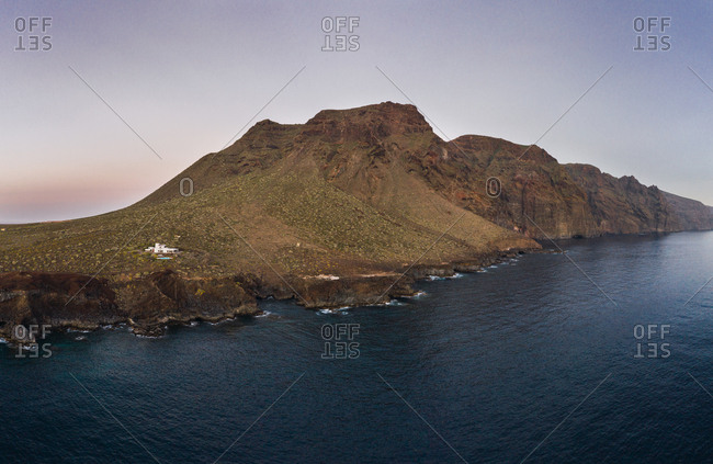 Drone view of rocky cliffs on remote coastline with dark rippled water of ocean, Tenerife, Spain