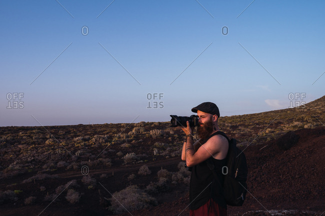 Side view of traveling man with backpack taking photo of landscape in dusky desert, Spain
